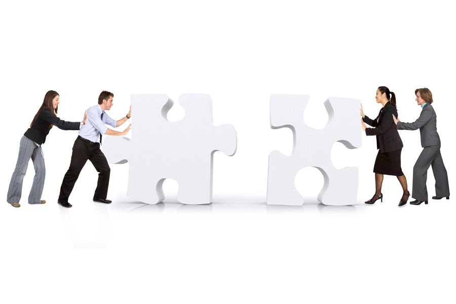 Image: People pushing two large puzzle pieces towards each other