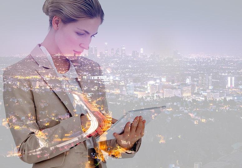 Bild: Office 365 Updates im Überblick, Frau mit Laptop vor Stadt