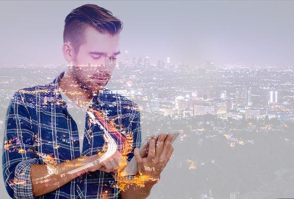 Bild: Mann mit Tablet vor Stadt, CONET Office 365 für Unternehmen, Office 365 Updates